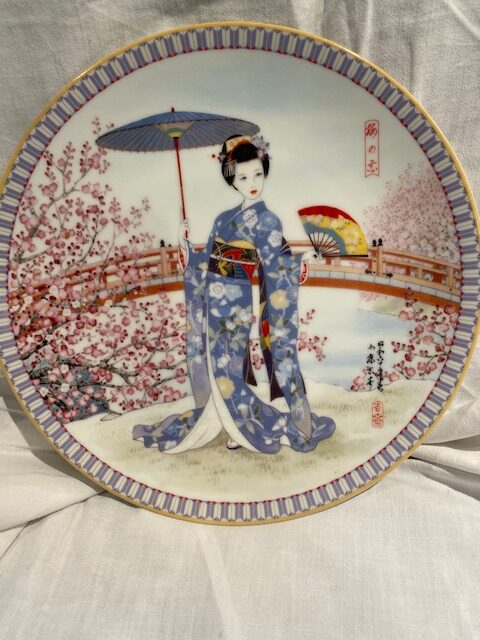 front of a collector plate - showing a Japanese woman in a blue floral kimono in front of a a red bridge and pink fruit tree blossoms