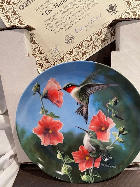 front of a collector plate - showing a male and a female ruby-throated hummingbird with red flowers