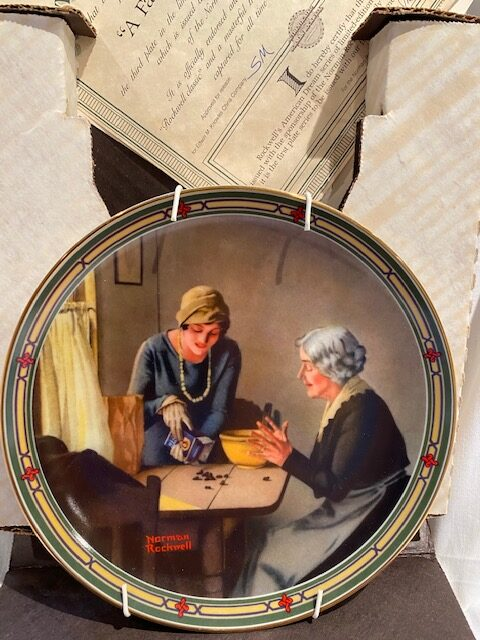 front of a collector plate - showing a younger woman and a older woman next to a table