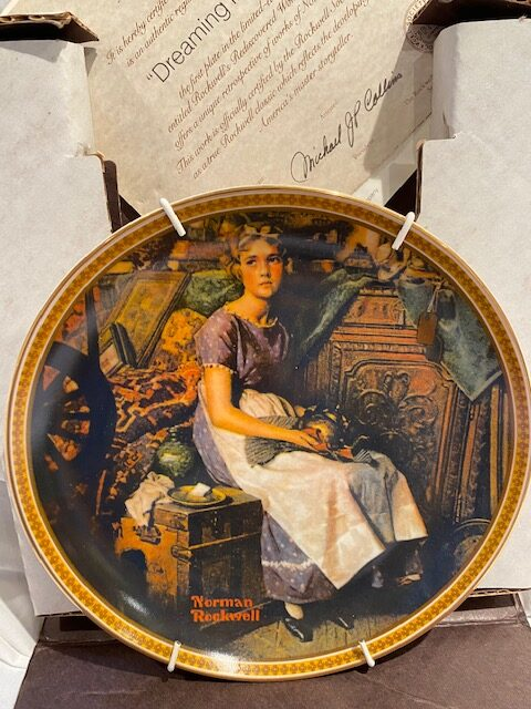 front of a collector plate - showing a girl seated in an attic with stored items